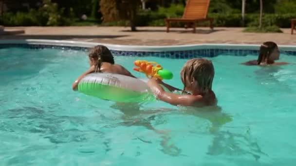 Kaukasischen Jungen spielen Schwimmen Baden mit Mädchen im Pool mit Wasserpistole und aufblasbaren Schlauch in slowmotion