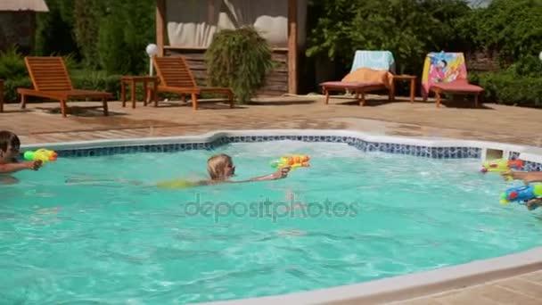 Vier kaukasischen Kinder spielen Schwimmen Baden im Pool mit Wasserpistolen und aufblasbare Röhren in slowmotion