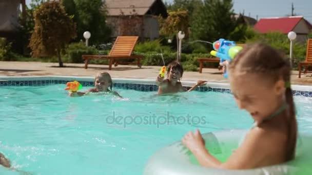 Zwei Mädchen mit aufblasbaren Schlauch schießen aus Wasserpistolen auf zwei Jungs im Pool mit slowmotion