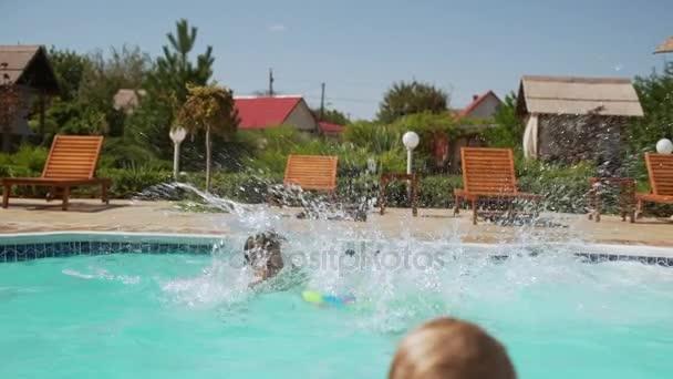 Mladá dívka Kavkazský s vodní pistole a nafukovací trubice skákání do bazénu, zatímco jiné děti si hrají plavecké koupací slowmotion