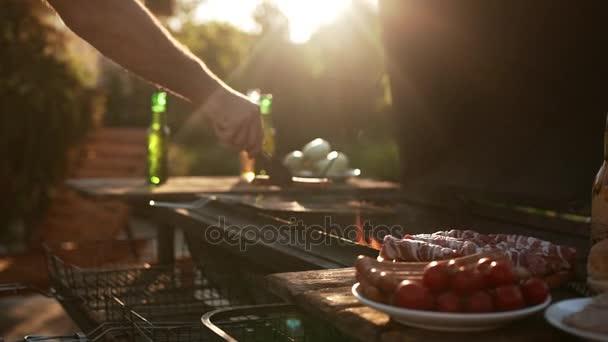 Mans ruka klade klobásy a maso na roštu grilování venku během slunce lesklý v slowmotion