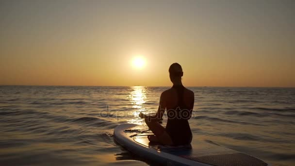 Young woman meditates sitting in yoga asana on supboard. Silhouette in slowmotion