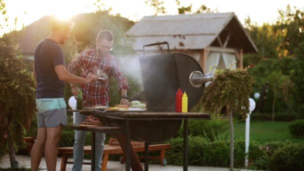 Dva belochu díky hamburgery se smaženým masem a buchty v blízkosti grilu v slowmotion