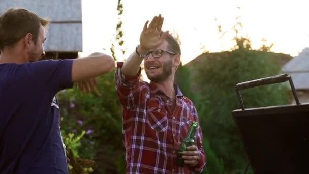 Dva šťastní belochu dávat vysoké pět navzájem pít pivo mluvící smějící se usmívá v slowmotion venku