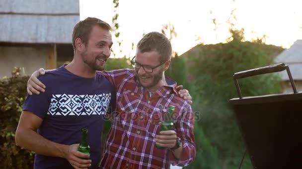 Huging dva kamarády navzájem ramena, stojící poblíž barbecue gril pití piva mluví, usmíval se smála slowmotion