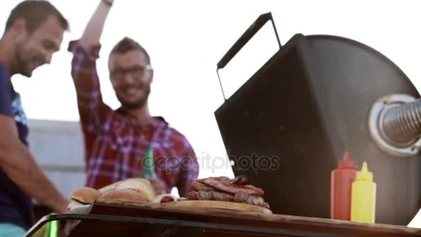Dva šťastné kamarády takže grilování s housky smažené klobásy a maso popíjeli pivo venku v slowmotion
