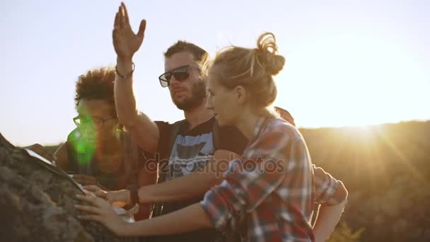 Three friends trying to find right direction using map and compass near big stone with sun on background. In slowmotion
