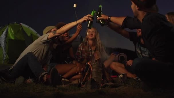 Six friends sitting by fire drinking bottled bear eating fried marshmallow cheering laughing talking smiling. In slowmotion