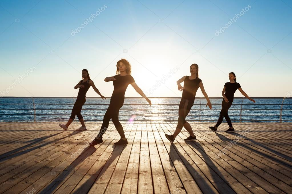 Silhouettes of sportive girls dancing zumba near sea at sunrise.