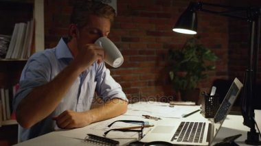 Young architect with blue shirt and light beard drinking from white cup that putting on glasses at table with computer and lamp. n slowmotion