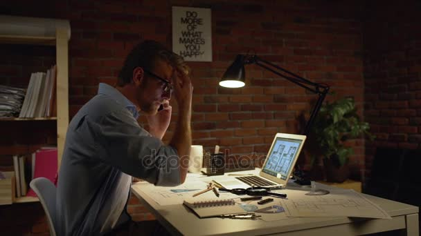 Fiatal koncentrált kaukázusi építész könnyű szakáll és beszél a mobil telefon, laptop és rajzok módosítása haj slowmotion asztalnál ülő kék ing