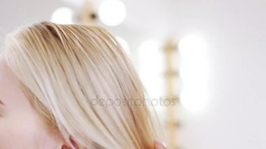 Hairdresser combing hair to blonde girl in beauty salon Slow motion Close up