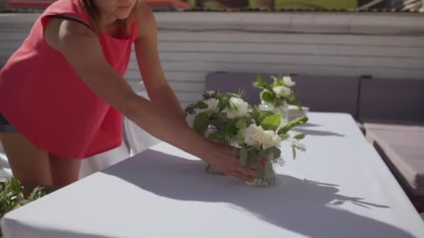 Kavkazský žena v růžové košili dávají květiny ve sklenicích na tabulkách přehodil s baldachýnem. V slowmotion