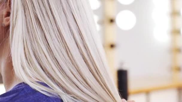Česání vlasy na blond dívka v salonu krásy zpomalené ženské kadeřník