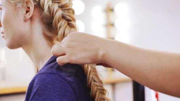 Donna parrucchiere che fa taglio di capelli per ragazza bionda nel salone di bellezza rallentatore