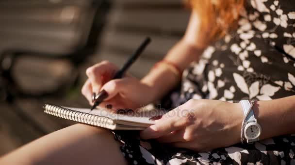 Mladá žena s rudými vlasy, psaní poznámek v programu Poznámkový blok v černé a bílé oblečení. Uzavírají v slowmotion