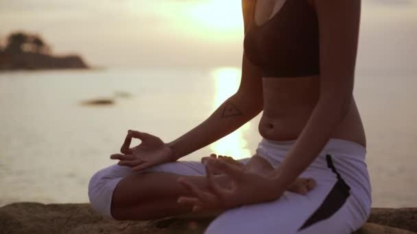 Young beautiful dark-skinned female sitiing meditating in yoga asana near sea. Silhouette
