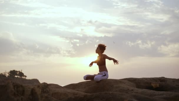 Young African American girl meditating in lotus posture on rocks and raising hands. Silhouette