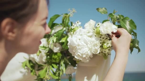 Close up footage of brown-haired female decorating wedding arch with flowers in slowmotion. Back view