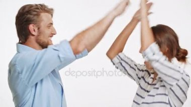 Young Caucasian couple gives high five with two hands to each other and smiling on white background