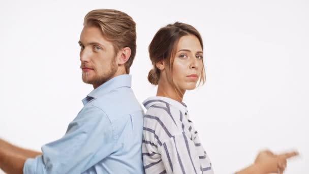 Veselá Kavkazský pár stojící zády k sobě hrát Představte si zbraně a ukázal do kamery na bílém pozadí