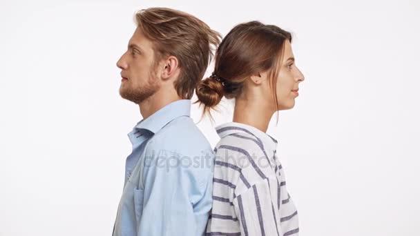 Úspěšné Kavkazský pár stojící zády k sobě na bílém pozadí. Pak se otočil a zobrazeno tlačítko fotoaparátu