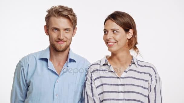 Beautiful Caucasian pair standing flirting ogle on white background. She bites lip, he kisses her