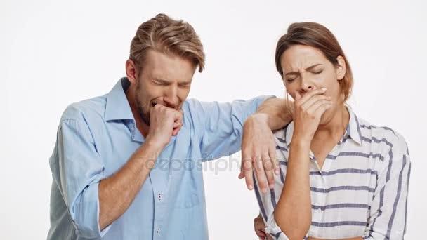 Mladý bělošský pár zíval na bílém pozadí a boji proti spánku