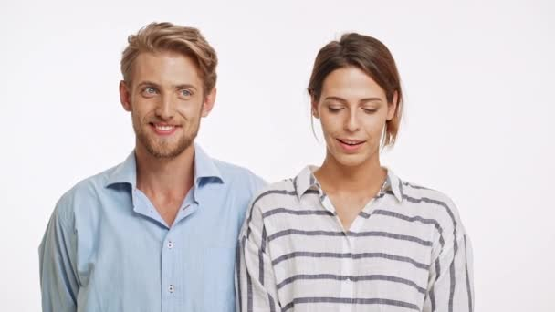 Beautiful Caucasian pair standing flirting ogle on white background in slowmotion. She bites lip, he kisses her
