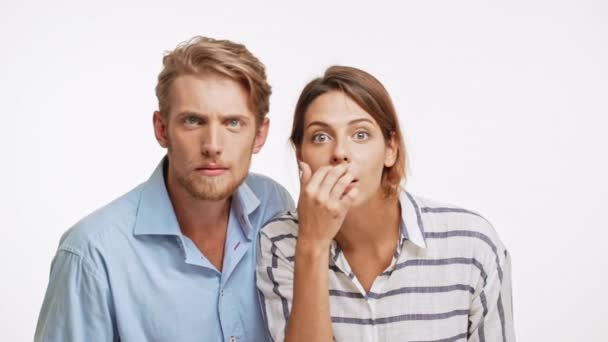 Young Caucasian pair looking at camera in slowmotion with suspicion and disapproval on white background