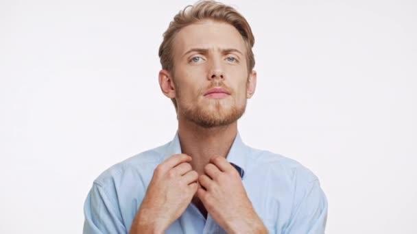 Pěkný bělošský vousatý muž s světle hnědé vlasy a modré oči upraví jeho límec a účes na bílém pozadí v slowmotion