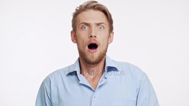 Překvapený mladý vousatý bělochovi s modré oči a hnědé vlasy při pohledu kamery s úžasem na bílém pozadí slowmotion