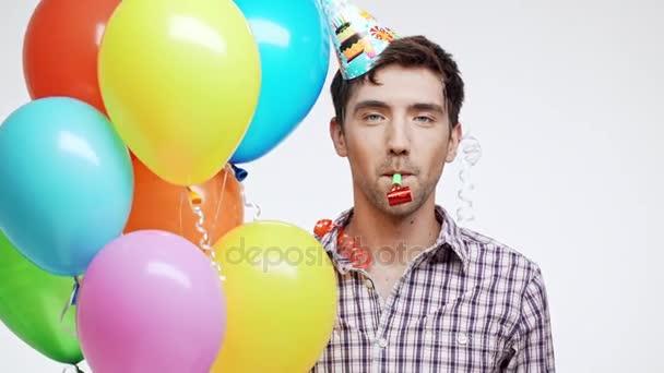 Šťastný mladý bělošský muž s tmavými vlasy a lehký Štětina nosit čepici narozeniny a různobarevné balónky zobrazeno ok na bílém pozadí