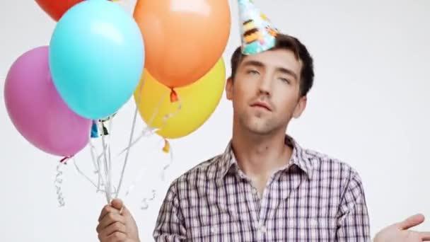 Aktivní mladý bělošský muž s tmavými vlasy a lehký Štětina tančí na bílém pozadí nosit čepici narozeniny a různobarevné balónky
