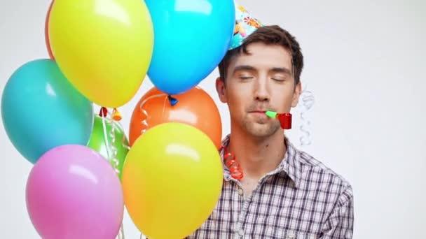 Jistý mladý bělošský muž s tmavými vlasy a lehký Štětina nosit čepici narozeniny a různobarevné balónky zobrazeno ok na bílém pozadí v slowmotion
