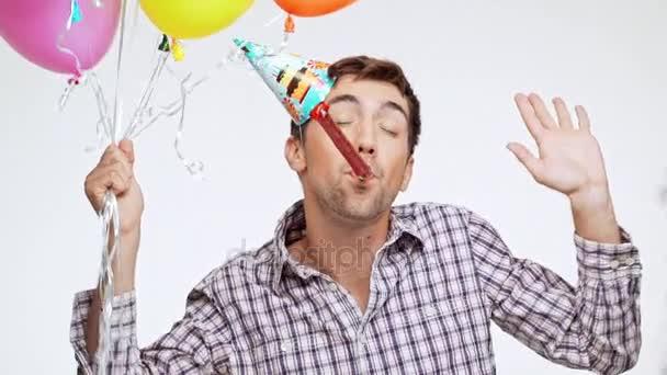 Aktivní mladý bělochovi s tmavými vlasy a lehký Štětina tančí na bílém pozadí nosit čepici narozeniny a různobarevné balónky v slowmotion
