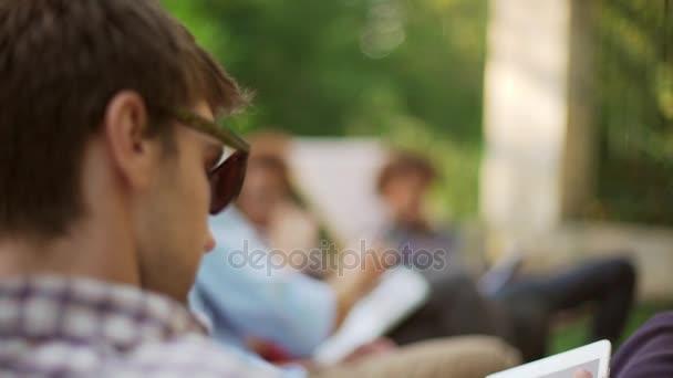 Interracial Gruppe von Männchen und Weibchen sitzen im Park auf Lounges mit Handys Laptop Tablet Lächeln, sprechen, plaudern in slowmotion