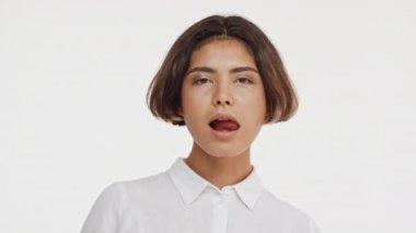 Mladá krásná bruneta východoasijské žena v košili flirtování na kameru s úsměvem zobrazeno jazyk, mávání rukou na bílém pozadí v slowmotion