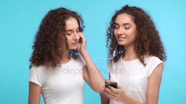 Two attractive Caucasian female twins in white t-shirts listening music on mobile phone through one pair of headphones dancing smiling on blue background in slowmotion