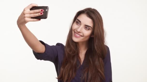 Krásná mladá žena Kavkazský dlouhé hnědé vlasy, na sobě modrou košili, takže selfie na mobilním telefonu pózuje s úsměvem mává rukou ukazující mír na bílém pozadí v slowmotion