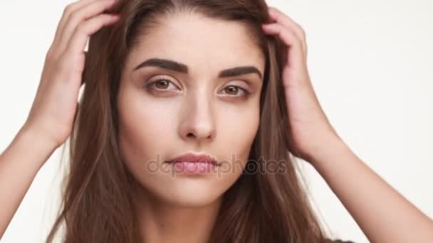 Beautiful Caucasian female with long brown hair standing on white background touching combing hair smiling. Close up footage