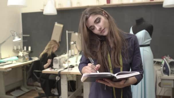 Obsazeno kavkazských brunetka mladé ženské postavení v šití učebny s notebookem mluvit na mobilním telefonu zároveň blond žena v černých šatech pracuje u stolu s počítačem
