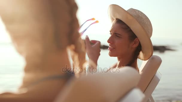 Two beautiful girls relaxing at the sea side sitting in chaise lounges. One trying on sunglasses of another. Slow motion.