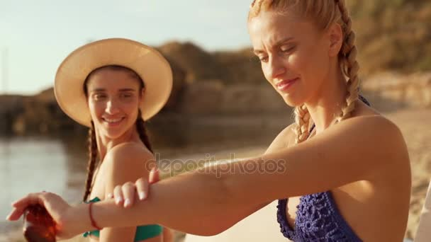 Two beautiful girls at the beach. One is rubbing suntan lotion on her arms. Slow motion.