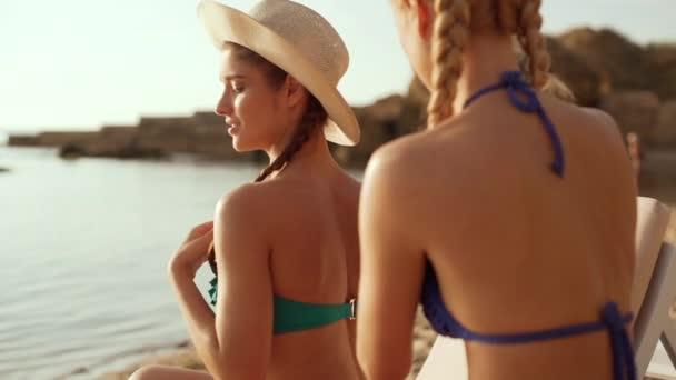 Két gyönyörű lány a tengerparton napozik a dörzsölés barnító krém elkészítése. Lassú mozgás