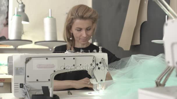 Blond krásná Kavkazský žena sedí u stolu s šicí stroj ve třídě pracovní