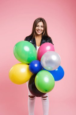 Woman in leather jacket posing with bunch of colored balloons