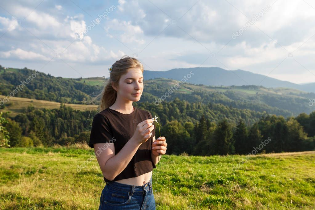 Beautiful blonde girl holding camomiles, carpathian mountains background.