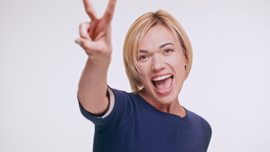 Kavkazská blond žena v modrou mikinu, stojící na bílém pozadí, smíchu, úsměvu mává rukou odesílání vzduch polibky říká Ano