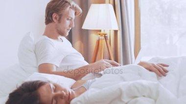 Muž pracuje na notebooku, spící přítelkyně